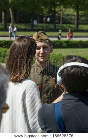 BERLIN - MAY 08 2016: Victory in Europe Day. Soviet War Memorial in Treptower Park. Journalist Ukrainian TV station 1+1 is interviewing a young man dressed in the form of a Soviet soldier during the war.
