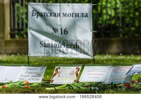 BERLIN - MAY 08 2016: Victory in Europe Day. Treptower Park. Mass grave of fallen soldiers and officers who liberated Berlin from the Nazis. Signs with names and date of death. The focus on the foreground.