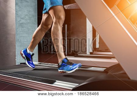 Side view full length of young man in sportswear running on treadmill at gym. Muscular young man in blue shorts doing exercises. Part of the body. Only legs. motion blur