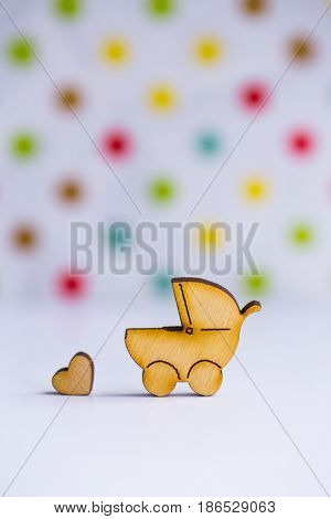 Wooden Icon Of Baby Buggy And Little Heart On Spotted Background