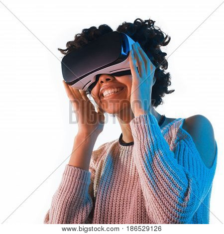 Beautiful female in sweater using VR headset and laughing on white backgrund.