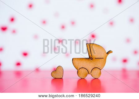 Wooden Icon Of Baby Buggy And Little Heart On Pink And White Background