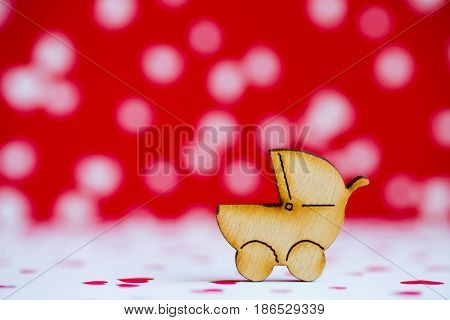 Wooden Icon Of Baby Buggy On Red And White Background