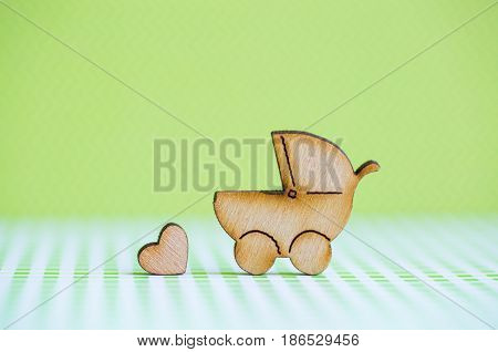 Wooden Icon Of Baby Buggy And Little Heart On Green Background