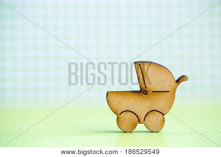 Wooden Icon Of Baby Buggy On Green Checkered Background