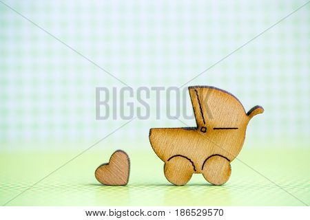 Wooden Icon Of Baby Buggy And Little Heart On Green Checkered Background