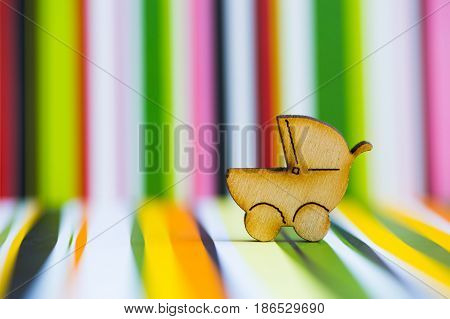 Wooden Icon Of Baby Buggy On Colorful Striped Background