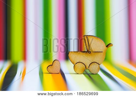 Wooden Icon Of Baby Buggy And Little Heart On Colorful Striped Background