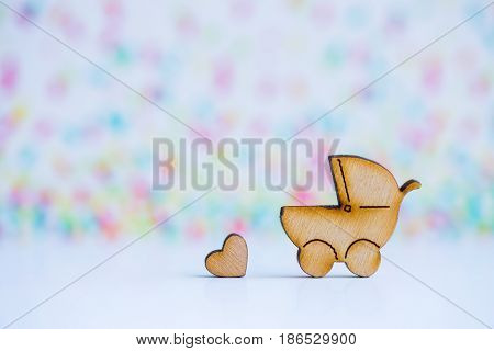 Wooden Icon Of Baby Buggy And Little Heart On Colorful Background