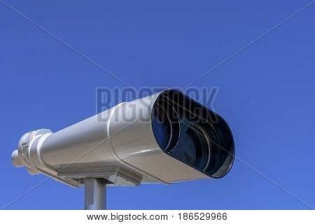 Stationary binoculars are placed against the blue sky