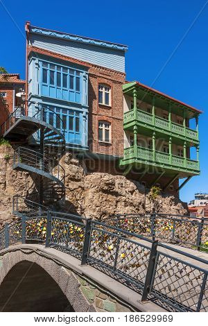 Bridge with padlocks a spiral staircase and residential houses on a rock in Tbilisi