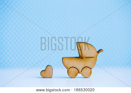 Wooden Icon Of Baby Buggy And Little Heart On Blue Background