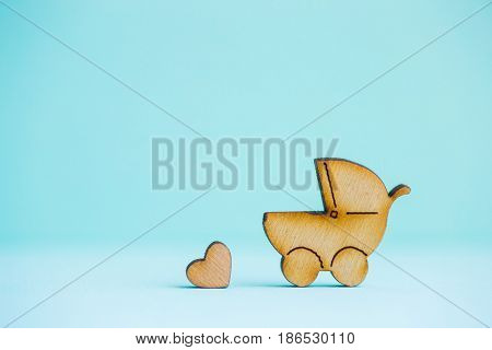 Wooden Icon Of Baby Buggy And Little Heart On Mint Background