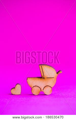 Wooden Icon Of Baby Buggy And Little Heart On Crimson Background