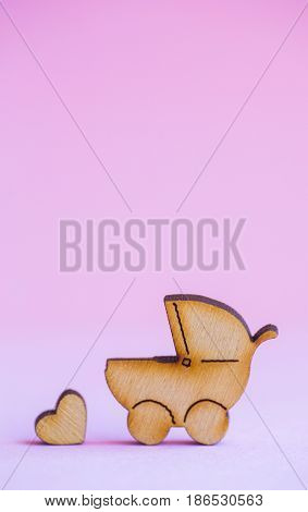 Wooden Icon Of Baby Buggy And Little Heart On Pink Background
