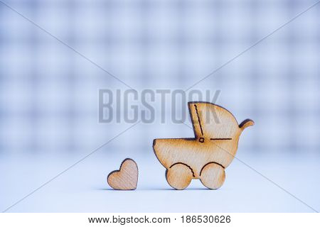 Wooden Icon Of Baby Buggy And Little Heart On Checkered Background