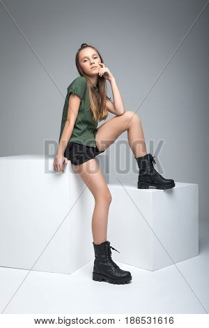 cute slender model sitting on white cube. woman dressed in green T-shirt, black shorts and large army boots