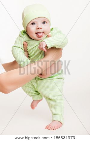 Walking toddler concept - little baby child boy making first step holding mother