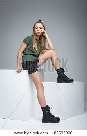 Young cute model sitting on big white cube. woman dressed in green T-shirt, black shorts and large army boots