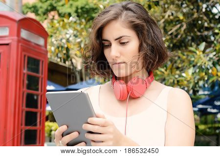 Woman With Red Headphones And Tablet.
