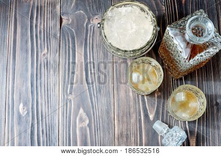 Glass Of Whiskey With Ice Cubes And Whiskey Bottle On An Old Wooden Table
