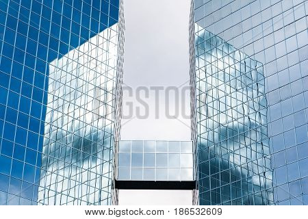 Two Skyscrapers linked by an overground connection reflecting clouds and sky in the glass fronts. The Commerce Place buildings in Hamilton, Ontario, Canada. CIBC. Canadian Imperial Bank of Commerce. FEBRUARY 2009.