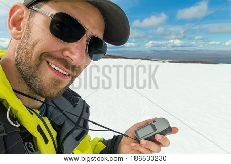 Smiling mountain guide using a GPS device on an icelandic glacier. He is happy to find his position on the digital map. Hiking on a volcano and glacier in Iceland.