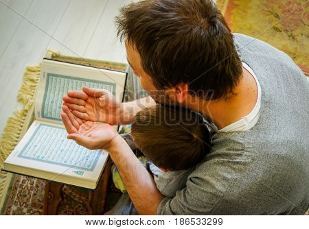 Young Arabic Muslim man reading Koran and praying