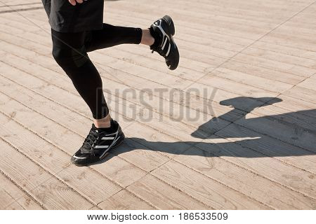 Horizontal outdoors shot of unrecognizable man running on wooden floor in sunny day.