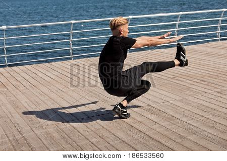 Side view of fit adult man bobbing on one leg on a pier. Horizontal outdoors shot.