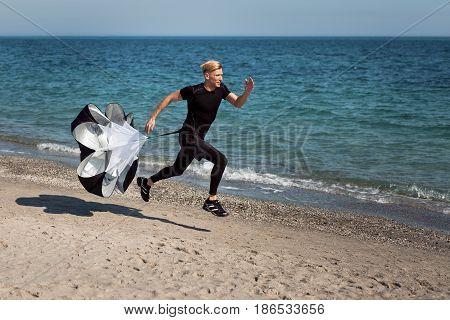 Horizontal outdoors shot of man running with parachute on sandy coast. Horizontal outdoors shot.