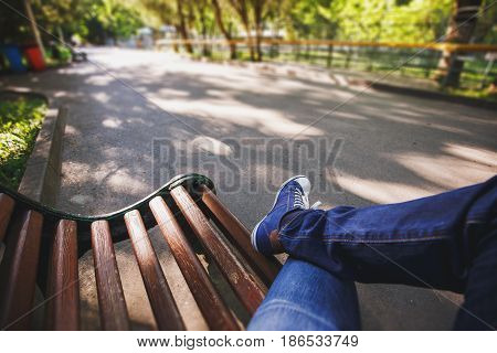 First-person view a man sitting on wooden bench in the park, wide angle