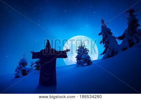 Silhouette of fairy wizard standing on a hill covered with fresh snow. Wonderful full moon rise in a mountain valley. Christmas mood. Night landscape.