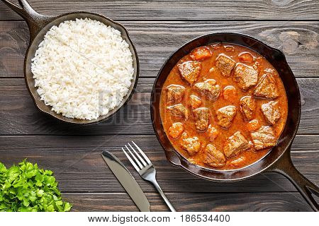 Homemade goulash traditional European beef meat stew soup spicy gravy food in cast iron pan with rice and parsley on rustic vintage wooden table background