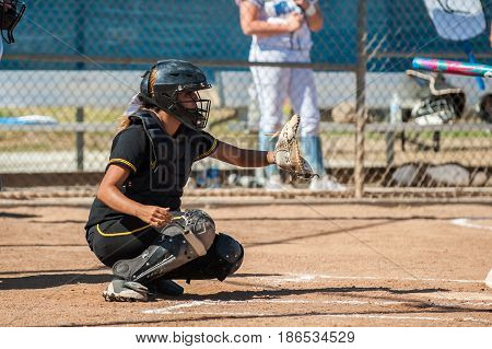 Softball catcher in black uniform reaching out with glove for pitch.