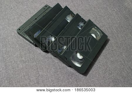 Five old video cassettes lie hardly gray background