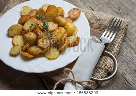 Roasted young potatoes with thyme in white plate.