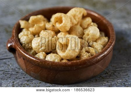 closeup of an earthenware bowl with pork rinds on a gray rustic wooden table