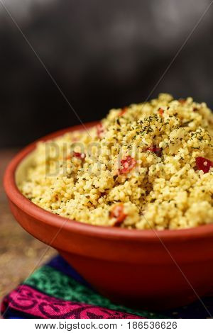closeup of an earthenware bowl with tabbouleh, a typical levantine arab salad, on a table set for lunch or dinner