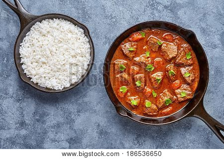 Goulash traditional homemade Hungarian beef meat stew soup food cooked with spicy gravy sauce in cast iron pan homemade meal served with rice on blue concrete kitchen table background.