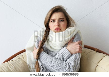 Young ill woman sitting on lounge at home