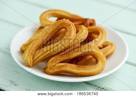 closeup of some churros typical of Spain on a white ceramic plate, placed on a pale green rustic wooden table