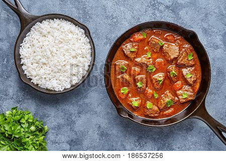 Goulash traditional Hungarian beef meat stew soup food cooked with spicy gravy sauce in cast iron pan homemade meal served with rice and parsley on blue concrete kitchen table background.