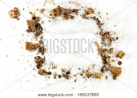 A frame made up by chocolate chips cookie crumbs, shot from above on a white marble background, with a place for text