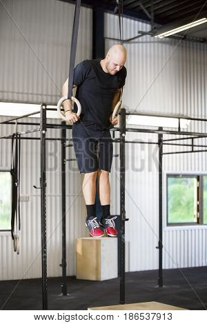 Full length of determined male athlete using gymnastics rings in health club