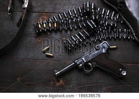 Gun Luger with cartridges and holster on the blackboard