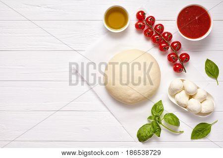 Raw pizza dough with baking recipe ingredients: mozzarella, tomatoes sauce, basil, olive oil, cheese, spices. Italian margherita preparation on white wooden table. Italian pizza margarita