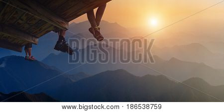Three tourists sit on a wooden flooring above the misty mountain valley and enjoy sunrise.