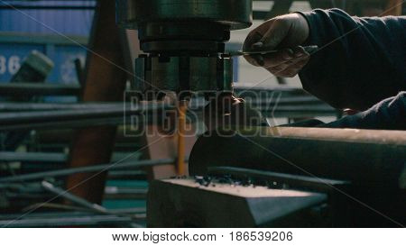 Close up of men's hands screwing the milling cutter on the milling machine