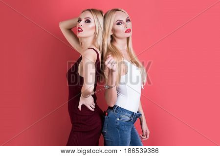 women. beautiful women in handcuff fashion cloth posing on pink background pretty blonde girl friends twins sisters having bright makeup homosexual and gay